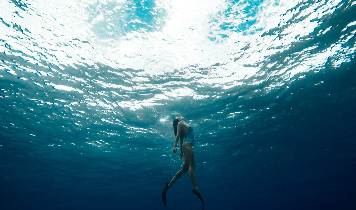 A woman swimming towards the surface of the water